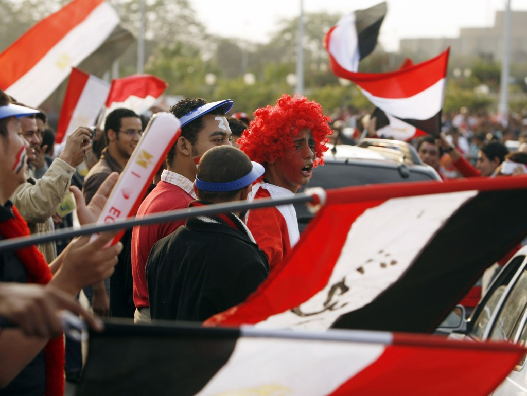 Egyptian soccer fans cheer with their national flags in front of Cairo stadium November 14, 2009. Egypt is hosting Algeria in their World Cup 2010 qualifying soccer match.  REUTERS/Asmaa Waguih(EGYPT SPORT SOCCER) Picture Supplied by Action Images *** Local Caption *** 2009-11-14T163822Z_01_CAI106_RTRIDSP_3_SOCCER.jpg