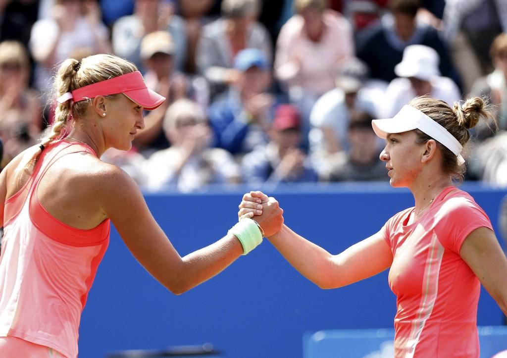 France's Kristina Mladenovic (L) shakes hands with Romania's Simona Halep